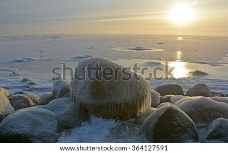 Frozen stones at the sea shore at the sunset - stock photo