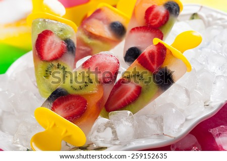 frozen strawberry,kiwi,peach and coconut water popsicles - stock photo