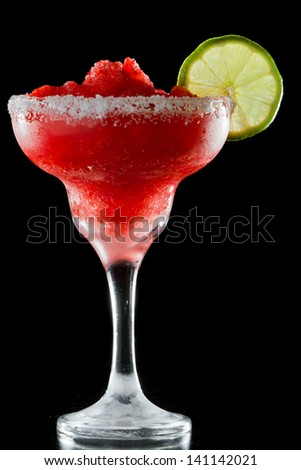 frozen strawberry margarita isolated on a black background garnished with a salt rim and a lime wheel - stock photo