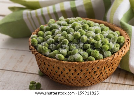 Frozen sweet peas in wooden bowl on white table. Selective focus. - stock photo