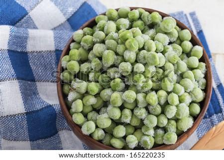 Frozen sweet peas in wooden bowl. Selective focus. - stock photo