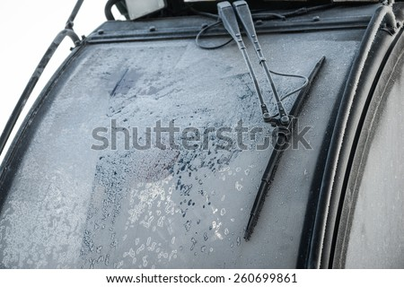 Frozen tractor window, texture freezing ice glass background. - stock photo