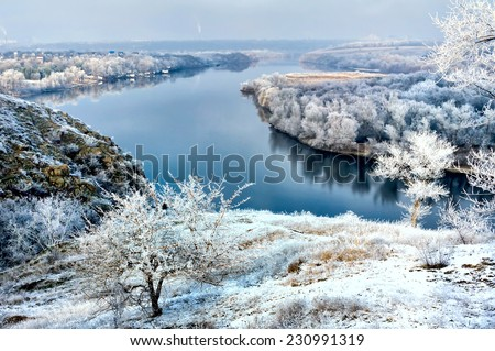 Frozen tree on winter field and blue river - stock photo