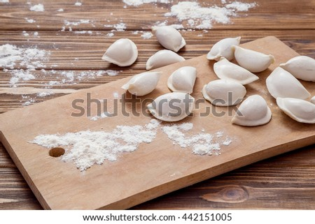 Frozen uncooked pierogi on wooden table - stock photo