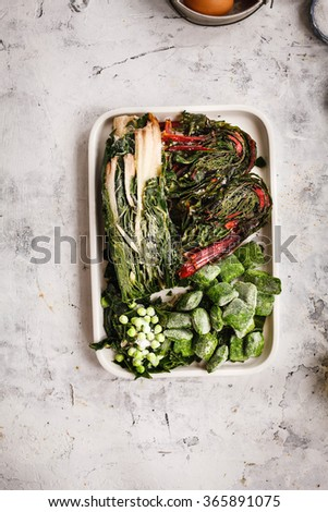 """Frozen vegetables. Frozen mangold or swiss chard """"Rainbow """", peas, beet root leafy and spinach leaves over stone table .top view. - stock photo"""