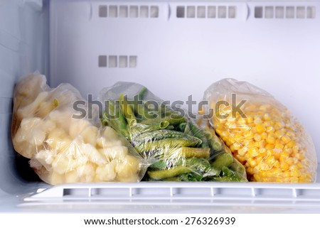 Frozen vegetables in bags in freezer close up - stock photo