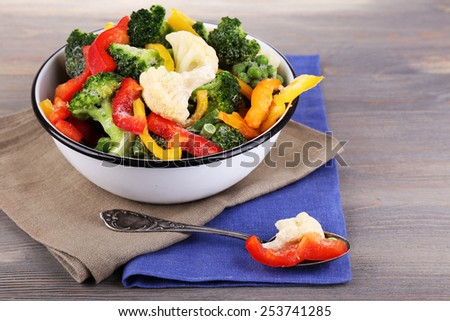 Frozen vegetables in bowl on napkin, on wooden table background - stock photo