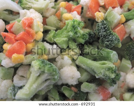 frozen vegetables in macro close up. You can see the icing on the broccoli and carrots. - stock photo