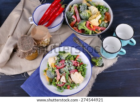 Frozen vegetables on plate on napkin, on wooden table background - stock photo