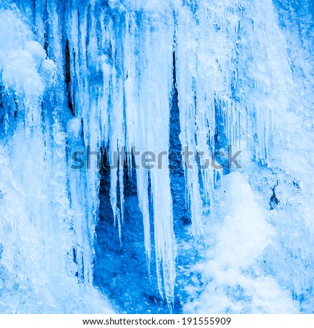 Frozen waterfall of blue icicles on the rock - stock photo
