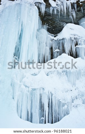frozen waterfall on a mountain stream in winter - stock photo