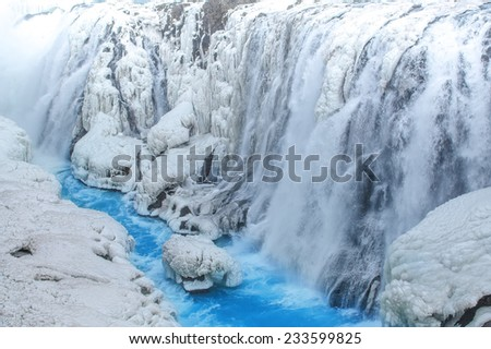 Frozen waterfall with clea blue water at early spring, Gullfoss, Iceland - stock photo