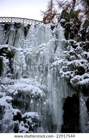 Frozen waterfall with icicles - seen in the park Wilhelmshöhe at bridge Teufelsbracke in Kassel, Germany - stock photo