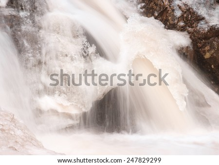 Frozen waterfall with water flowing under the ice. - stock photo