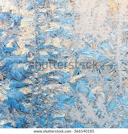 frozen window glass with frosty pattern and sunlight - stock photo