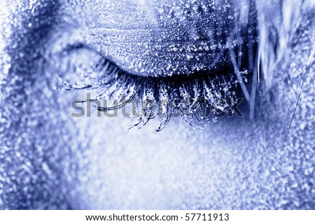 Frozen woman's eye covered in frost. Close-up shot toned in blue - stock photo