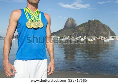 Frst place athlete wearing gold medals standing outdoors at Botafogo Bay Rio de Janeiro Brazil  - stock photo