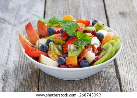Fruit and berry salad on wooden table, close-up - stock photo