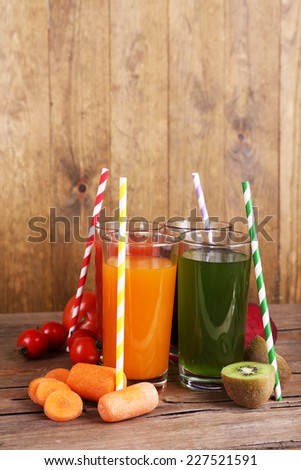 Fruit and vegetable juice in glasses and fresh fruits and vegetables on table on wooden background - stock photo