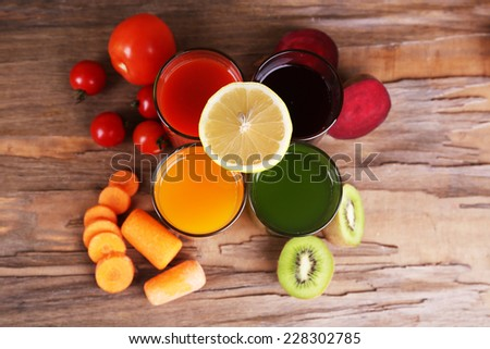 Fruit and vegetable juice in glasses and fresh fruits and vegetables on wooden background - stock photo
