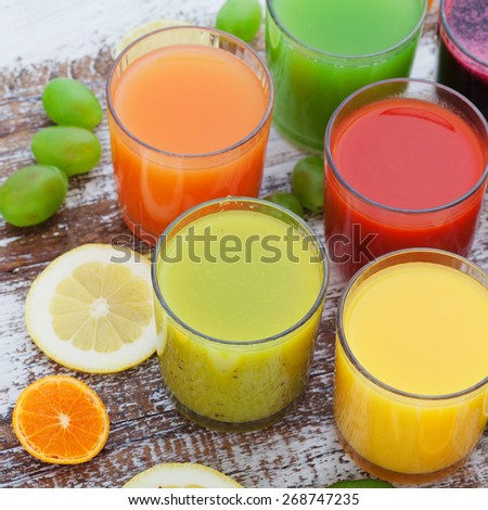 Fruit and vegetable juice in glasses and fresh fruits on wooden table summer background - stock photo