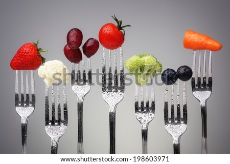 Fruit and vegetable of silver forks against a grey background concept for healthy eating, dieting and antioxidant
