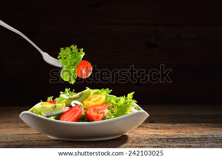 Fruit and vegetable salad in a bowl and picked by a fork on wooden background - stock photo