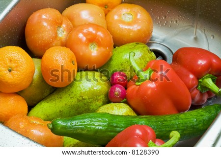 Fruit and vegetables are put in a kitchen sink for washing - stock photo