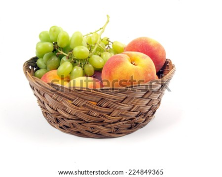 fruit basket of peaches and grapes on a white background
