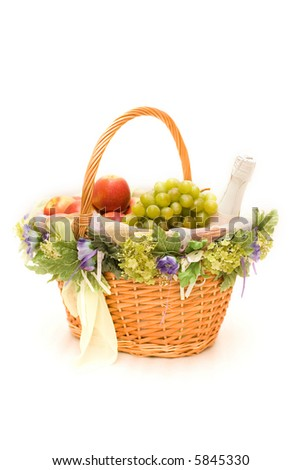 Fruit basket with a bottle of champagne on white - stock photo