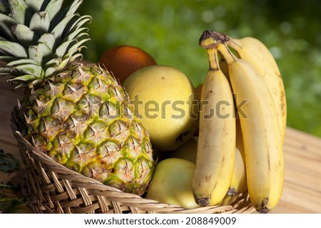Fruit basket with apples, pineapple and bananas - stock photo