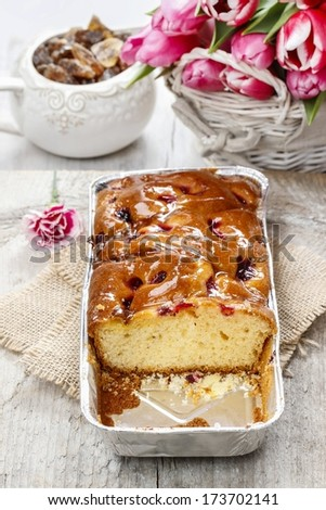 Fruit cake in rectangular pan. Bouquet of pink tulips in the background