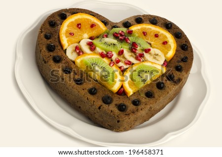 Fruit cake in shape of a heart - stock photo