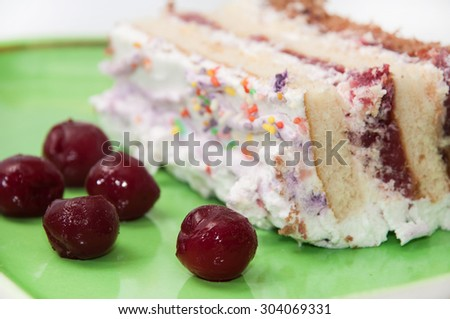 Fruit cake with cherries on green plate with frozen cherries. - stock photo