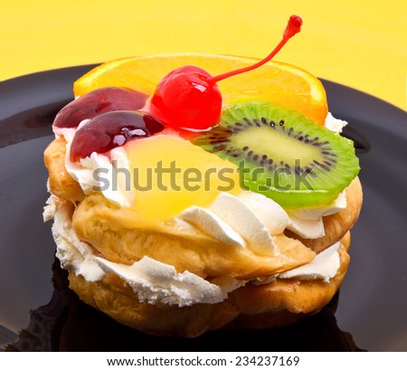 fruit cake with cream on black plate on yellow background - stock photo