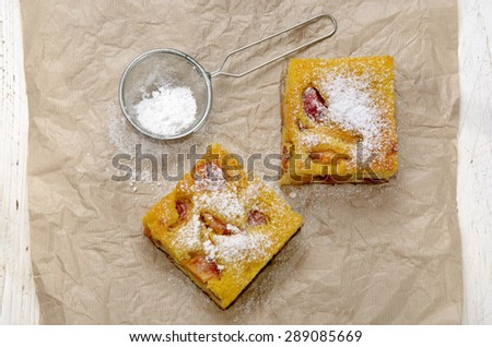 fruit cake with nectarines, kitchen paper, sieve, powdered sugar on wooden table - stock photo