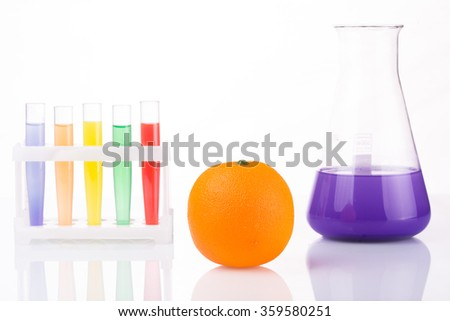 Fruit close chemical test tubes. Genetic Engineering. pesticides in foods - stock photo
