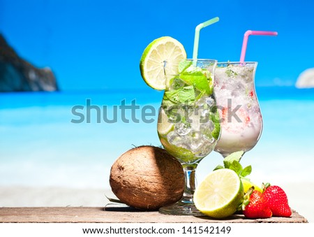 Fruit cocktail and Mojito with blue beach on background - stock photo