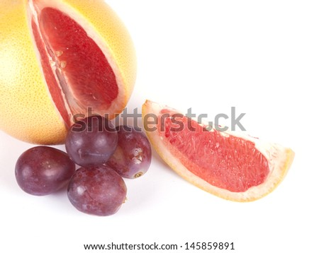 Fruit composition of ripe grapefruit and grapes on a white background - stock photo