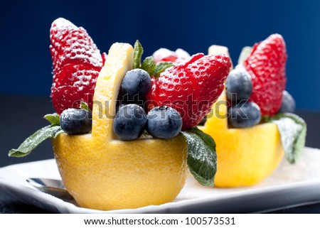 Fruit composition: strawberry and blueberry in a lemon basket with mint leaf