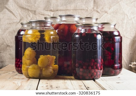 Fruit compote in glass jars on a wooden table