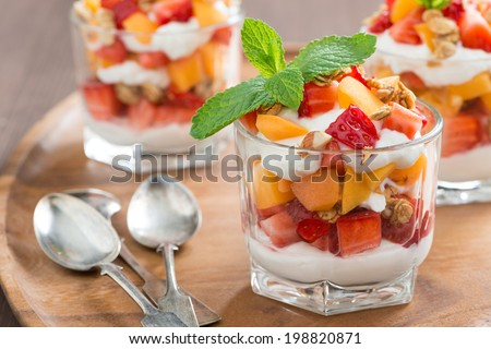 fruit dessert with whipped cream, mint and granola, close-up, horizontal - stock photo