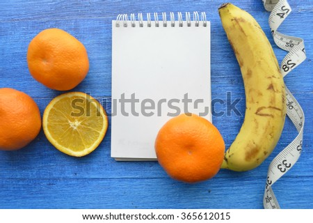fruit diet.On diet.Fresh oranges , bananas,tangerines. Diet for Weight Loss.healthy eating, healthy lifestyle concep.Measuring tape