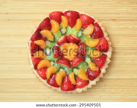 Fruit Flan - A delicious homemade dessert on a wooden table. - stock photo