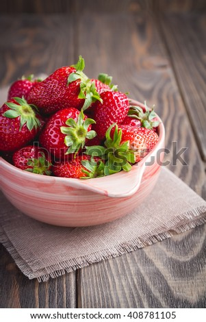 fruit. Fresh ripe strawberries in a bowl on old wooden background - stock photo
