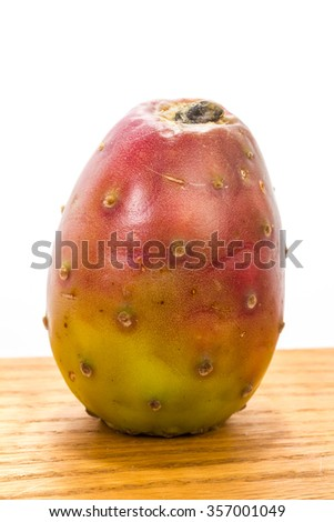 Fruit from Prickly Pear on wood counter top against white background with copy space.  Sometimes called Tuna or Cactus Fruit is popular ingredient in gourmet health conscious dishes. - stock photo