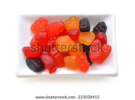 Fruit gummi candies assortment in white plate on white  - stock photo
