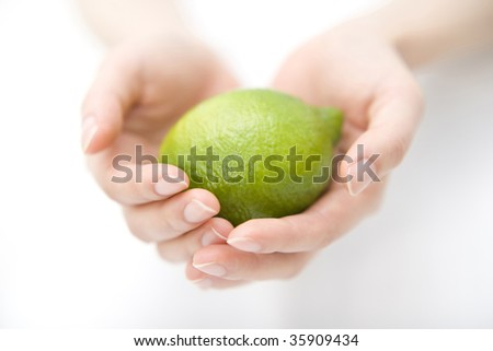 FRUIT IMAGE-a fresh lime with woman's hands isolated on white