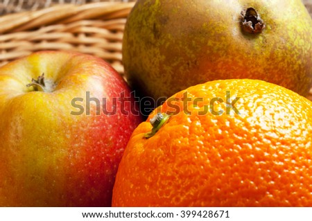 Fruit in a basket. Close up of an orange, apple and pear. Citrus and orchard fruit. - stock photo