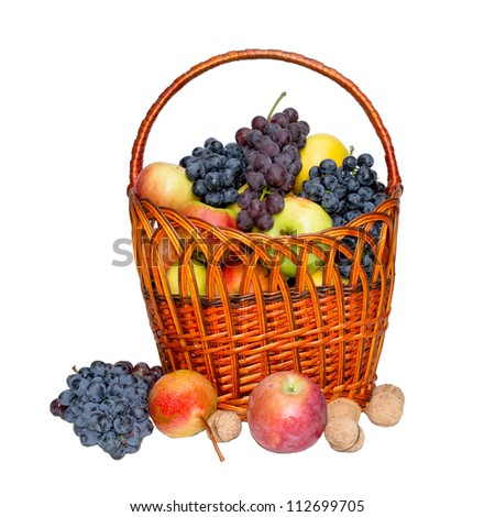 Fruit in a wattled basket on a white background. Apples, grapes, pears, nuts. - stock photo